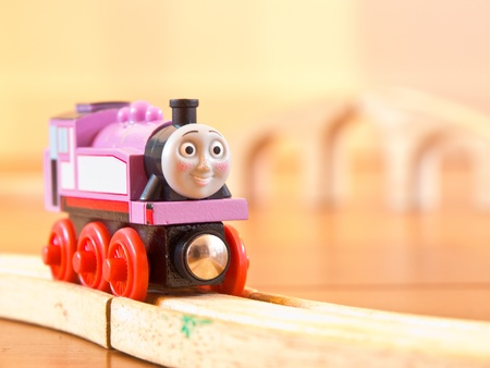 Rosie the pink Thomas the train on a wooden railroad photo