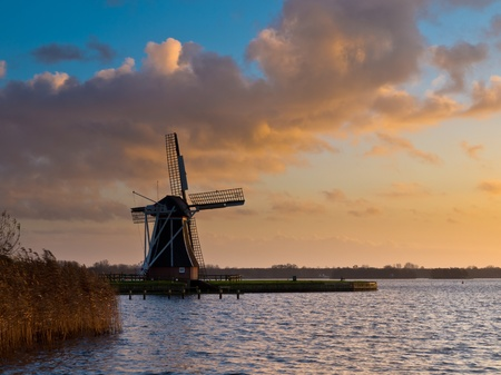 traditional dutch windmill during windy orange sunset photo