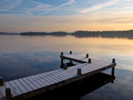 granular: Jetty at lake in winter during sunrise