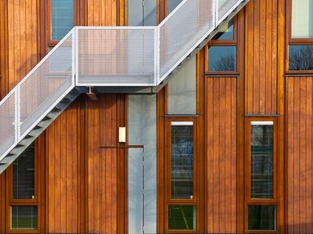 Escaleras de metal en una fachada de madera moderna Foto de archivo