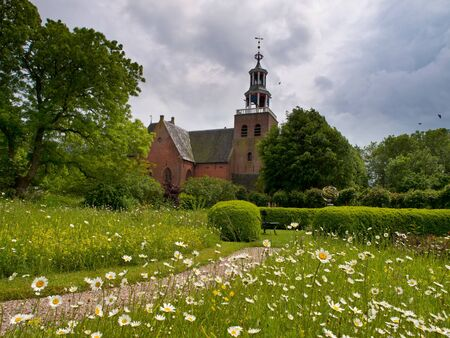 birds scenery: The church of the dutch village of pieterburen under a  dramatic sky Stock Photo