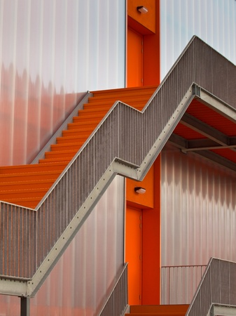 Orange escape stairs on the outside of a modern building photo