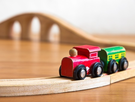 Red and green wooden toy train on railroad with bridge in backdrop photo