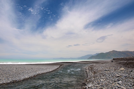 kaikoura: River mouth at a pebble beach, Kaikoura coast New Zealand