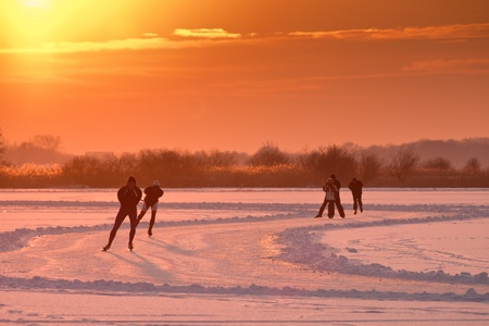 winterday: Dutch speed skaters are back lit by setting sun