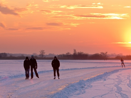 Group of ice skaters during sunset on natural ice photo