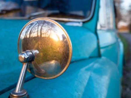 spiegelbeeld: Achteruitkijkspiegel op een vintage auto die lijkt op terugkijken in de tijd, concept