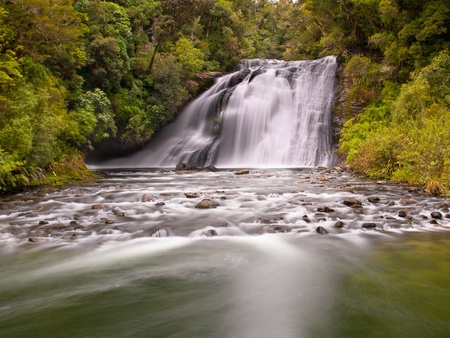 Long exposure image of a waterfall in a lush rainforest in new zealand photo