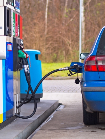 Blue car at gas station being filled with fuel against inflated prices