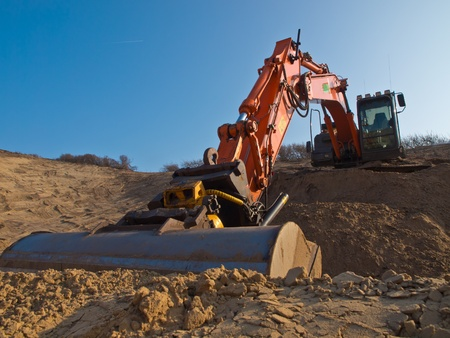 Orange colored heavy construction digger in a large sandpit