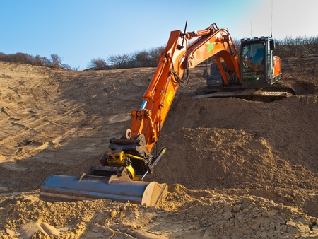 power shovel: Heavy orange excavator at work in a sandpit seen from the front