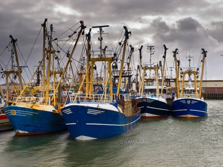 brooding: Modern fishing boats under a brooding sky in a dutch fishing harbor