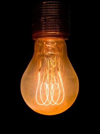 incandescent: Old dusty light bulb  glowing in the dark