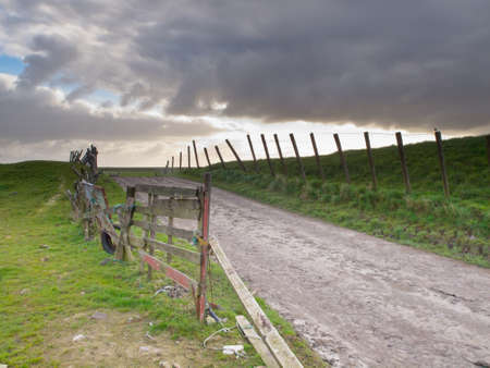 brooding: Rural road over a dutch dike under a brooding sky