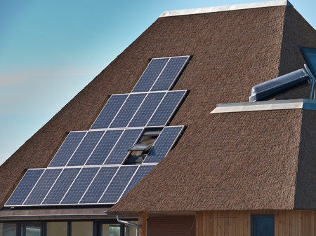 Solar panels on a modern house with thatched roof Stock Photo - 13334970