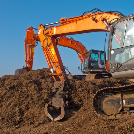 Two orange excavators during sunset on a building site Stock Photo - 13334769