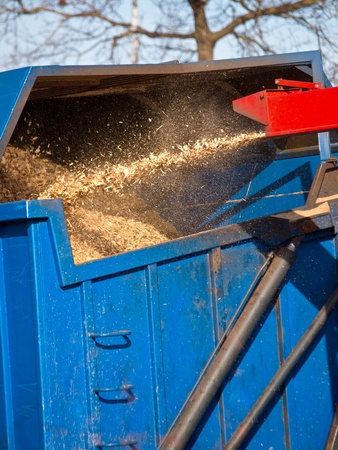 expel: Wood Chipper Machine Filling Back Of Truck With Mulch Stock Photo
