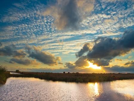 turba: Cielo nublado dramático sobre el Parque Nacional de los Natherlands durante la puesta de sol