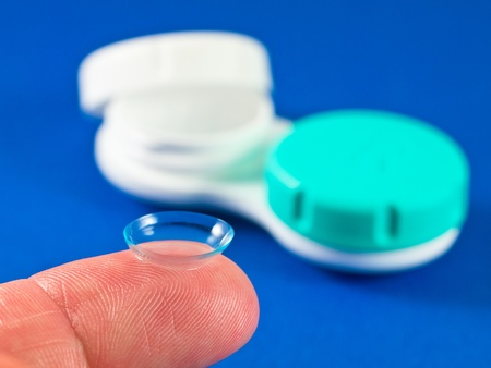 finger tip: Contact lens on finger tip wit blue background