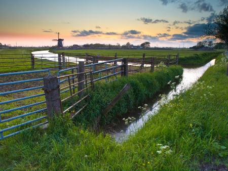 Typical dutch landscape with fences during sunset photo