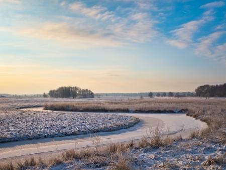 frozen river in agricultural landscape