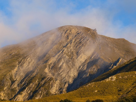 A rocky alpine mountain top is covered in clouds photo