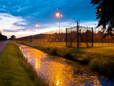 European Prison Fence with Ditch at Dawn Stock Photo - 16627385