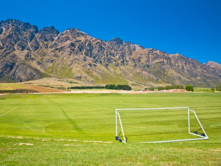 Sports ground in mountain setting with a soccer goal on foreground photo