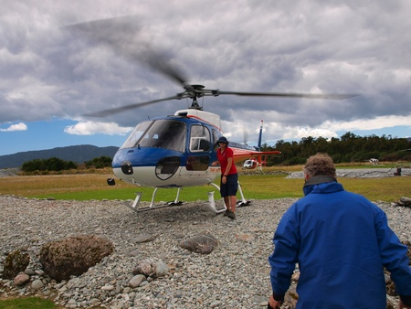 aboard: Tourist is going aboard an adventure helicopter to the new zealand wilderness