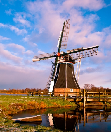 Dutch Windmill on the Waterfront of a Lake with Spectacular Clouds Stock Photo - 17325084
