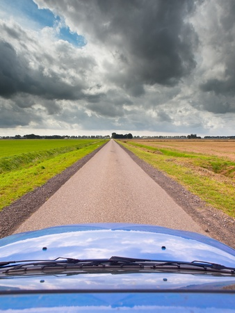 Blue Car on a Long Straight Road with Dark Cloudy Sky as a Concept for an Uncertain Economic Future Stock Photo - 18234593