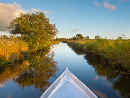 Bow of a Rowing Boat in the Evening with Blurred Background Because of the Movement photo