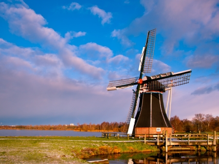 dutch landmark: Dutch Windmill on the Waterfront of a Lake with Spectacular Clouds