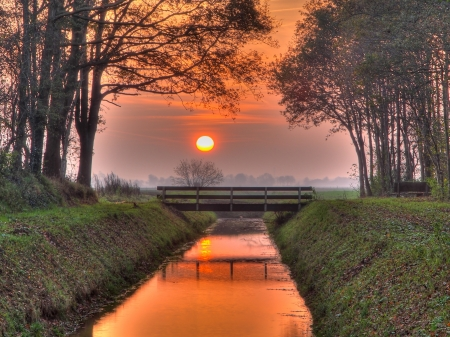 Sunset over bridge and ditch in a park Stock Photo