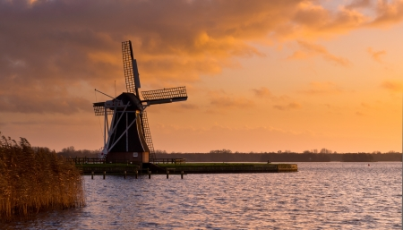 dutch windmill: Dutch Windmill on the Waterfront of a Lake with Spectacular Clouds