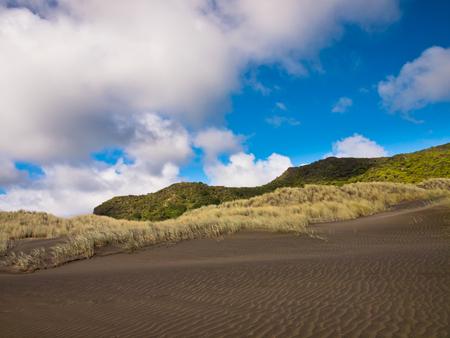 Dark sand dunes under a cloudy summer sky in New Zealand photo