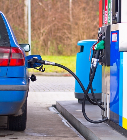fillup: Blue car at gas station being filled with fuel against inflated prices