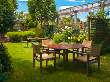 landscaped garden: Landscaped Garden with Wooden Dining Table Set in the Shade of Trees Stock Photo