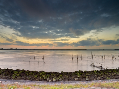dike: Sunset over the Waddensea seen from a Dike with Poles and Fishing Netsfrom Stock Photo