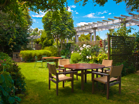 backyards: Landscaped Garden with Wooden Dining Table Set in the Shade of Trees Stock Photo