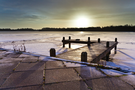 Amber Colored Sunrise above a Jetty on a Frozen Winter Lake with Ice and Snow