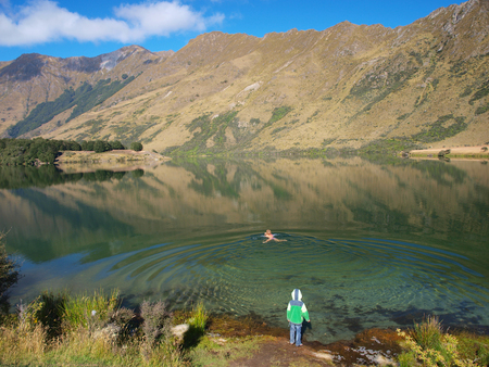 Woman Swimming in the Serene Waters of Moke Lake, Queenstown, New Zealand photo