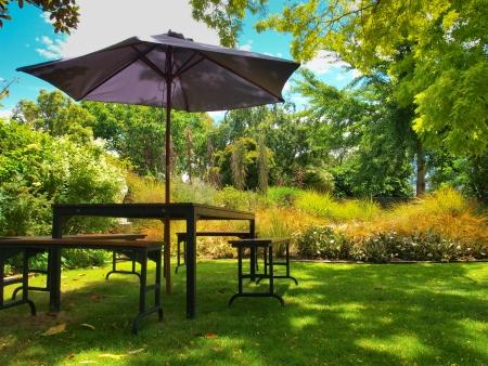 Eettafel met stoelen en parasol in de schaduw in een weelderige tuin