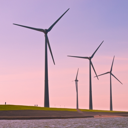 megawatt: Giant 3 Megawatt Wind Turbines along the Sea Dike in the Netherlands seen from the Water