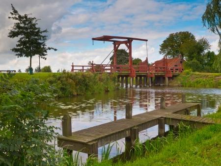 drawbridge: Old Wooden Drawbridge over a River in European Countryside Boating Area Stock Photo