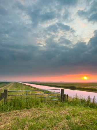 agricultural area: Sunrise over the Horizon in Agricultural Area with Canal and Gate in the Netherlands
