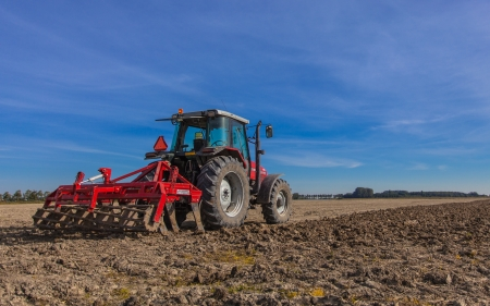 Farming in the Netherlands, Tractor with Plough in a Field under Blue Sky