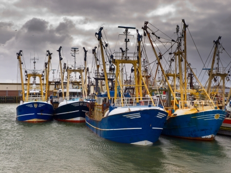 fishing industry: Modern fishing boats under a brooding sky in a dutch fishing harbor