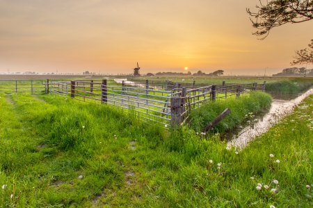 Dutch Landscape with Windmill and Fences during Sunset photo