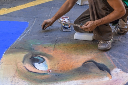 Street Artist Drawing a Portrait on the Pavement photo
